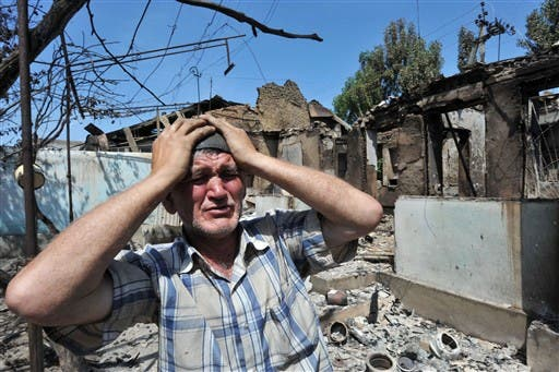 An Ethnik Uzbek holds his head in his hands as he stands beside the wreckage of his burned out home in Osh on June 14, 2010