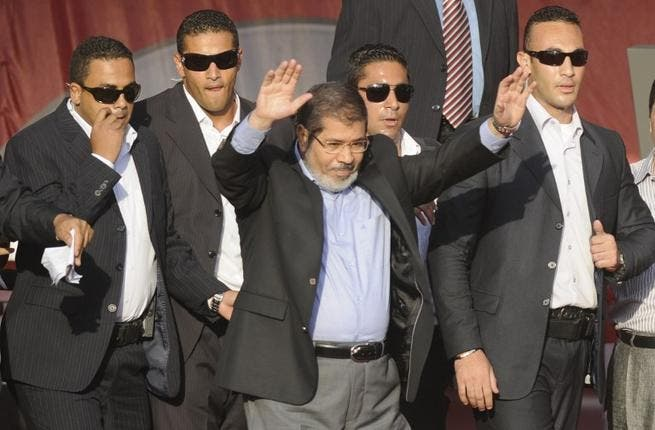 In better times: Flanked by bodyguards, Morsi saluted tens of thousands of Egyptians Tahrir Square on June 29, 2012, when he symbolically swore himself in as the country's first elected civilian president. (AFP PHOTO/MOHAMMED HOSSAM)