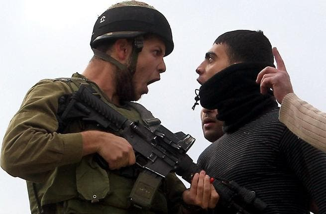 A Palestinian resident of the northern West Bank village of Madama argues with an Israeli soldier after security forces came to intervene in clashes between Palestinian farmers and Israeli settlers from the Yitzhar settlement, on Monday. (AFP PHOTO/JAAFAR ASHTIYEH)