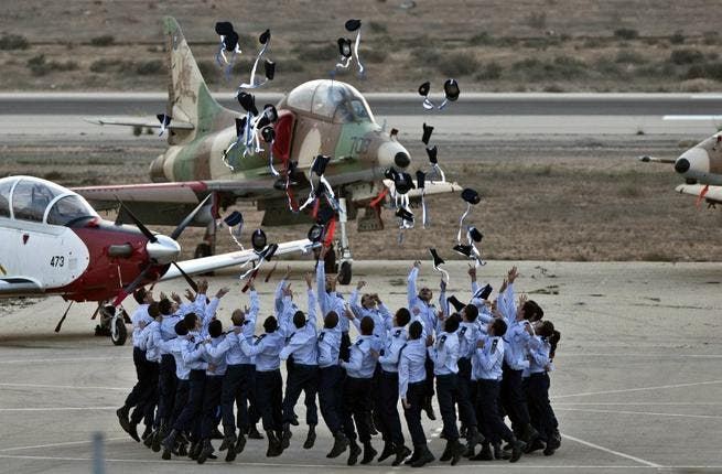 Israeli pilots throw their hats in the air as they celebrate at their graduation ceremony. (AFP)