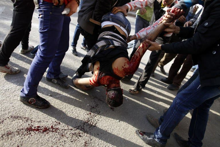 Egyptian protesters carry their gravely injured comrade during clashes with riot police near Tahrir Square in Cairo on March 9, 2013. Two protesters were killed in the clashes in Cairo --one from bird shot and one from suffocation. (AFP PHOTO / MAHMOUD KHALED)