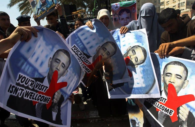 Relatives of prisoners of Palestinians held in Israeli jails burn pictures of US President Barack Obama during a protest against his visit to the region at the Jabalyia refugee camp, in the northern Gaza Strip. (AFP PHOTO / MAHMUD HAMS)