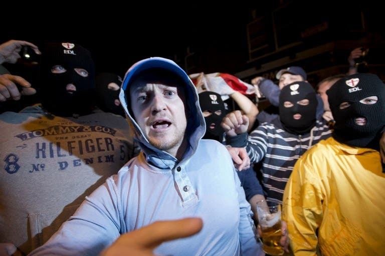 Members of the English Defence League (EDL) wear balaclavas as they gather outside a pub in Woolwich in London on May 22, 2013 after a man believed to be a serving British soldier was brutally murdered nearby in what Prime Minister David Cameron said appeared to be a terrorist attack (Justin Tallis / AFP)