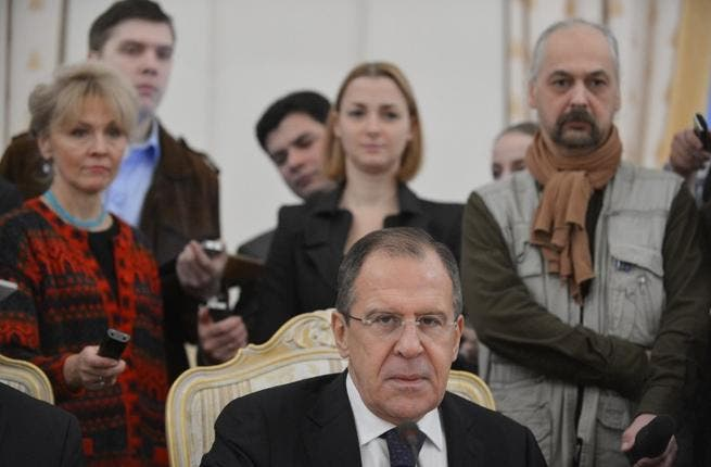 Russia's Foreign Minister Sergei Lavrov is circled by journalists in Moscow on Friday, as he meets his visiting Egypt counterpart Mohamed Amr on the Syrian crisis. (AFP PHOTO / NATALIA KOLESNIKOV)