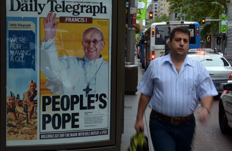 A man walks past an advertising billboard displaying the front page of Sydney's tabloid newspaper the Daily Telegraph with picture of Pope Francis, Argentina's Jorge Mario Bergoglio. (AFP PHOTO/ Saeed KHAN)