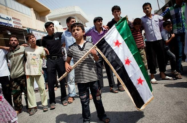 In August this year a boy holds a pre-Baath Syrian flag, that was adopted by the Syrian revolution during the uprising. (AFP PHOTO / ACHILLEAS ZAVALLIS)
