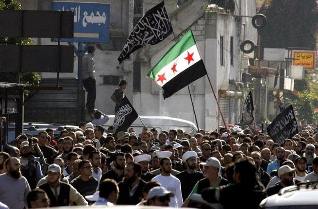Protestors hold a Syrian pre-Baath flag during a demonstration lead by Lebanese Salafis on Sunday in Southern Lebanon. (AFP PHOTO/MAHMOUD ZAYYAT)