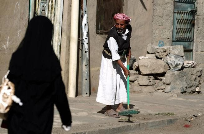 A Yemeni man sweeps a street during the