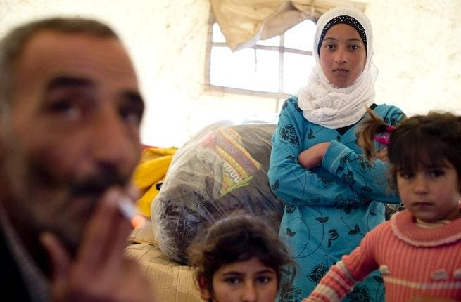 A Syrian refugee family gathers inside a tent after fleeing from the northern Syrian town of Darkush.( AFP PHOTO / ODD ANDERSEN)