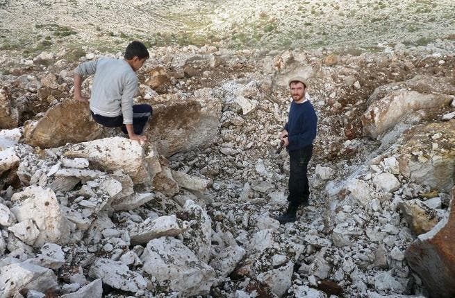 Syrian men stand inside a crater where they said a Scud missile landed near the military base of Sheikh Suleiman on the outskirts of the northwestern town of Darret Ezza on Friday. (AFP PHOTO / HERVE BAR)