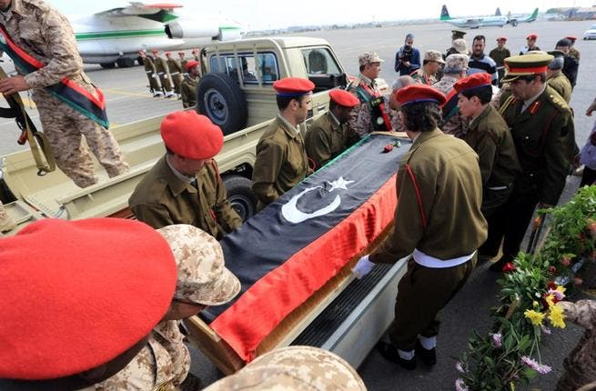 Libyan army soldiers carry the coffin of one of two soldiers killed in action in the oasis town of Bani Walid during a memorial service at Mitiga Airport, in Tripoli, on Sunday. (AFP PHOTO/MAHMUD TURKIA)