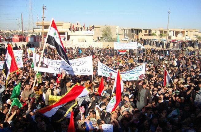 Iraqi protesters hold banners during a demonstration demanding the ousting of Prime Minister Nouri al-Maliki on Friday. (AFP)
