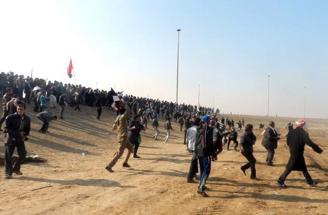 Iraqis throw stones after protestors attacked Iraq's deputy prime minister Saleh al-Mutlak on Sunday. (AFP)