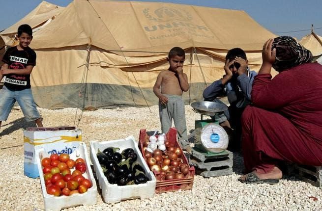 A Syrian refugee woman sells vegetables at the Zaatari refugee camp, (AFP PHOTO/KHALIL MAZRAAWI)
