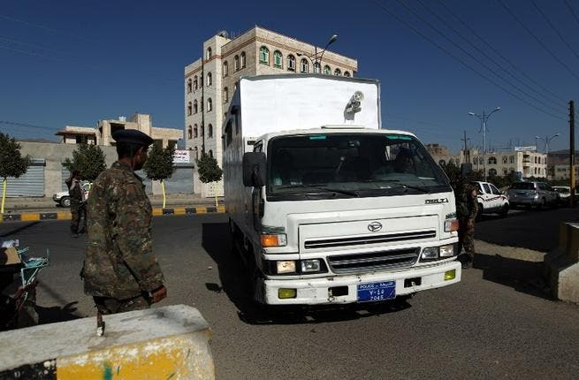 Yemeni soldiers stand guard outside the state security court as suspected Yemeni al-Qaeda militants arrive in a truck for their trial. (AFP PHOTO/ MOHAMMED HUWAIS)