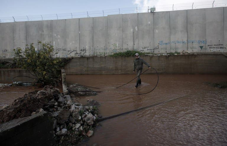 A Palestinian boy stands in a flooded area adjacent to Israel's controversial separation barrier near the West Bank city of Qalqilya (AFP PHOTO/JAAFAR ASHTIYEH)