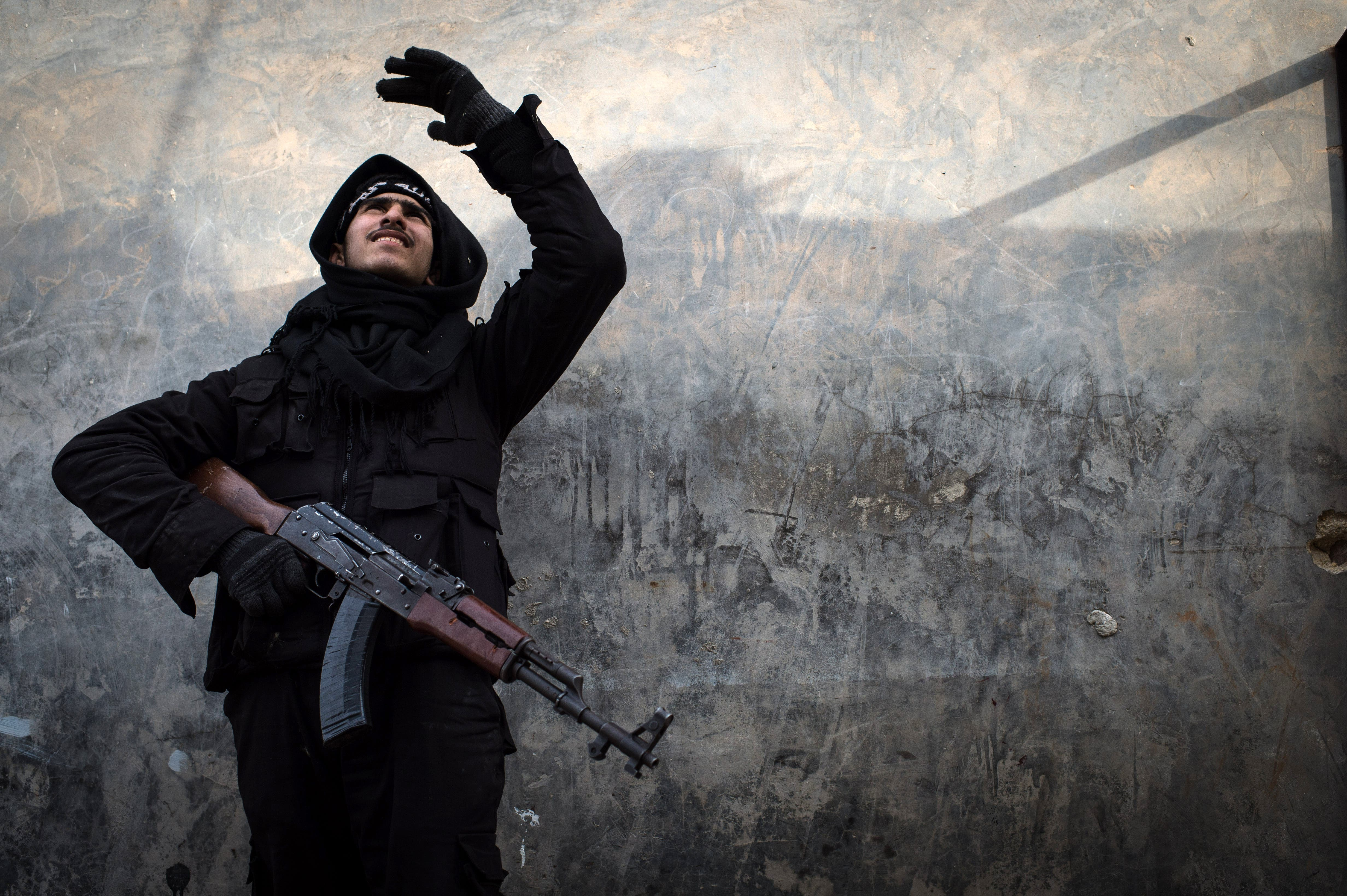 A Rebel fighter points at smoke rising in the city of Aleppo on Friday. UN leader Ban Ki-moon has warned that Syria is in a