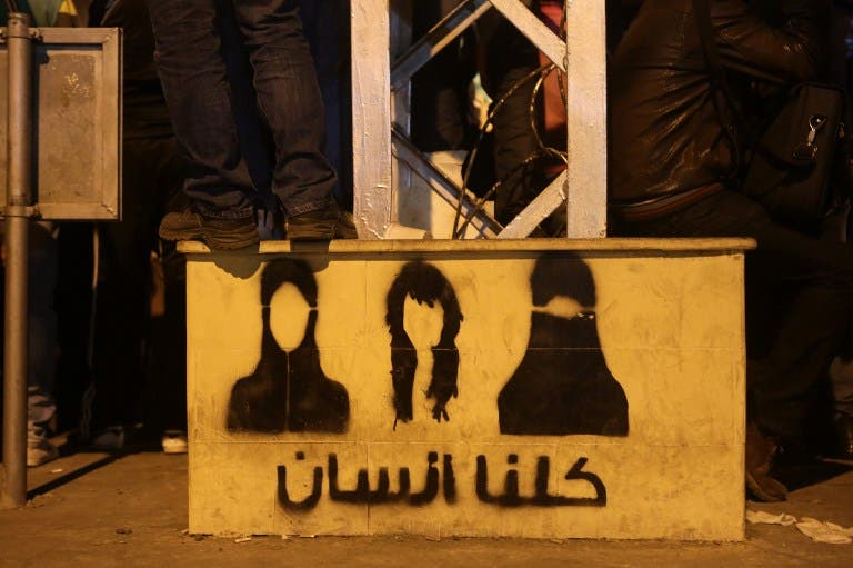 An opposition supporter stands on top of a step painted with graffiti and Arabic writing that reads,