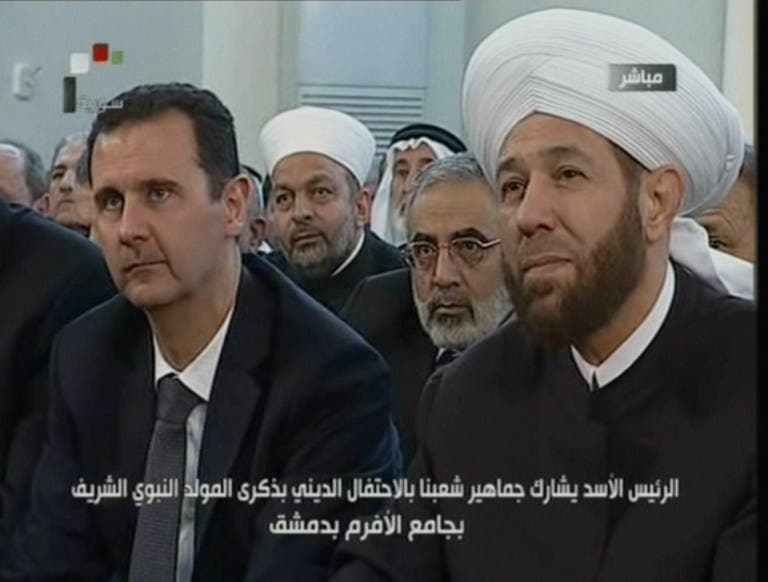 An image grab taken from the state-run Syrian TV shows Syria's President Bashar al-Assad (L) siting next to Syrian Grand Mufti Ahmed Hassun. (AFP PHOTO/SYRIAN TV)