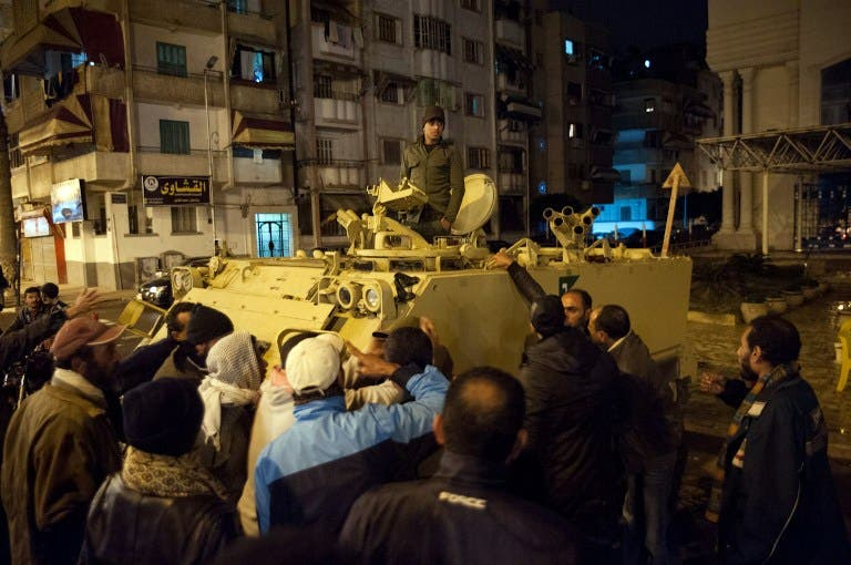 Egyptian protestors shout at a soldier standing in an armored personnel carrier as they demonstrate in the streets of the canal city of Port Said. (AFP PHOTO / STR)