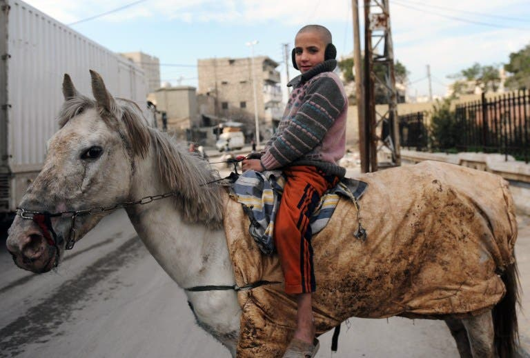 A Syrian child poses on a horse in the northern city of Aleppo. (AFP PHOTO/BULENT KILIC)
