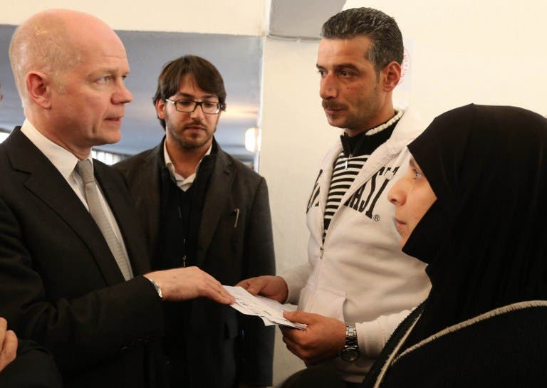 British Foreign Secretary of State for Foreign Affairs William Hague (L) talks with Syrian refugees (R and 2ndR) at a World Food Programme Center in Burj Hammoud's area on the northern outskirts of Beirut. (AFP PHOTO POOL MOMAMED AZAKIR)