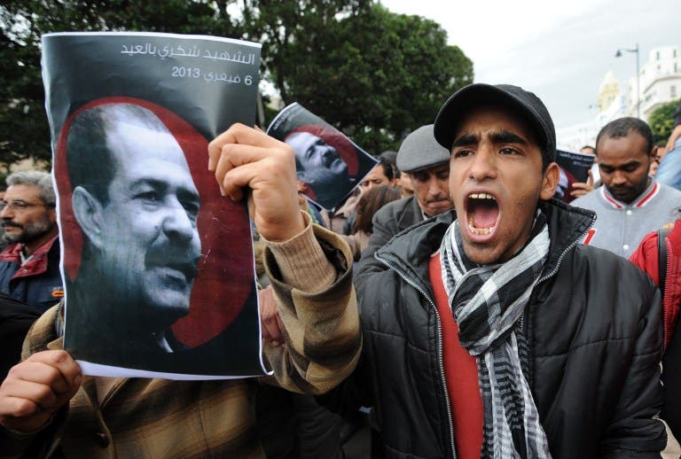 A Tunisian protester holds a placard featuring killed opposition leader Chokri Belaid during a demonstration on Saturday. (AFP PHOTO / FETHI BELAID)
