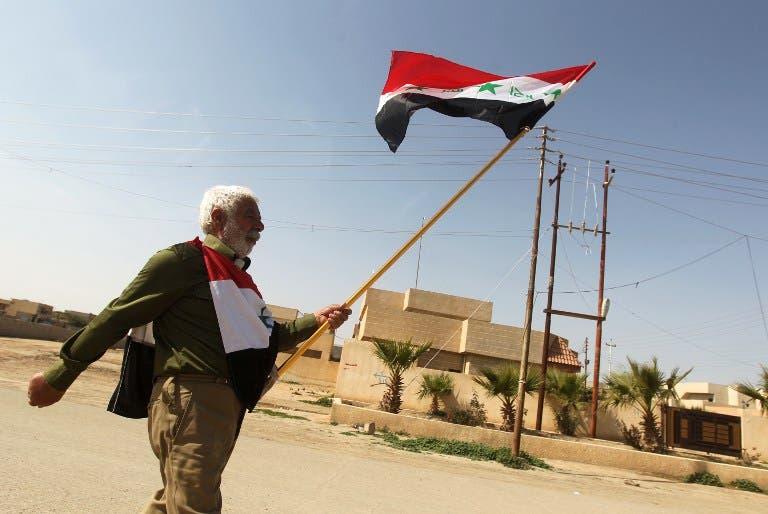 A man holds the Saddam-era national Iraqi flag as he walks in Tikrit. (AFP PHOTO/AHMAD AL-RUBAYE)