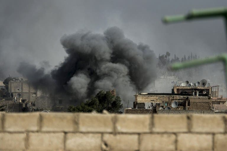 Smoke rises from the site of a missile attack in Hawiqah neighborhood in the eastern Syrian town of Deir Ezzor on Tuesday. (AFP PHOTO/ZAC BAILLIE)