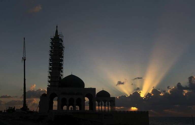 A mosque under construction is silhouetted as the sun sets along the seafront in Gaza City. (AFP Photo / MAHMUD HAMS)