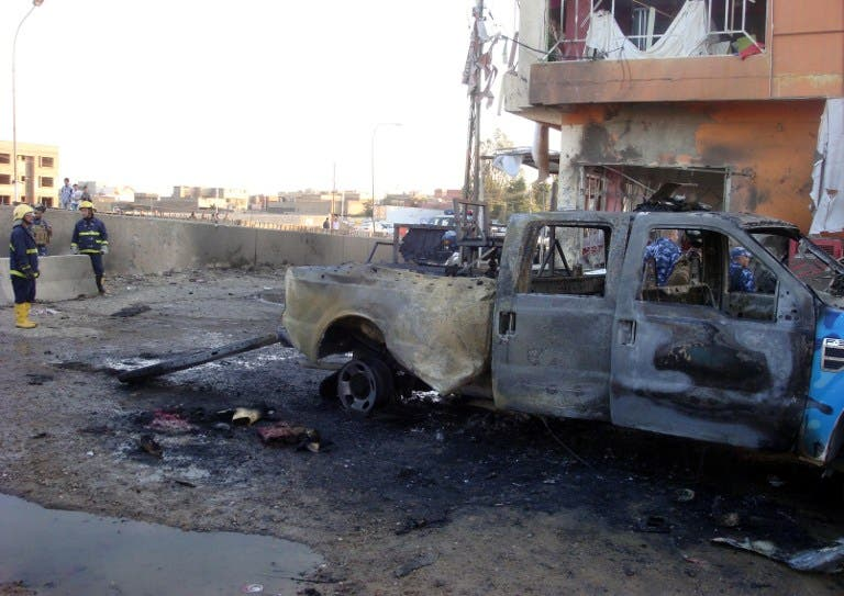 Iraqi security and fire fighters secure the scene following a car bomb, in the northern city of Kirkuk on March 5, 2013. (AFP PHOTO/MARWAN IBRAHIM)