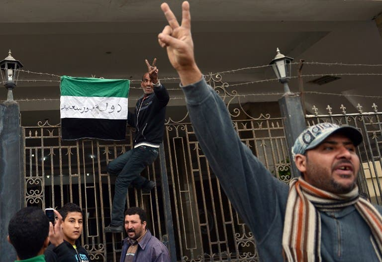 An Egyptian protestor flashes the sign for victory as he puts a flag with writing on it reading in Arabic: