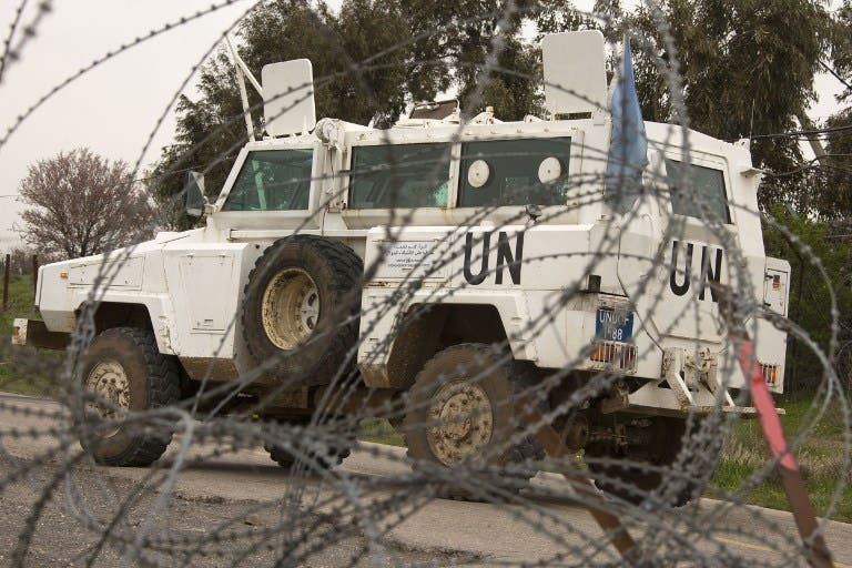 A UN vehicle is seen driving behind barbwire as UN peacekeepers leave a post, in the demilitarised United Nations Disengagement Observer Force (UNDOF) zone, in the Golan Heights. (AFP PHOTO/JACK GUEZ)