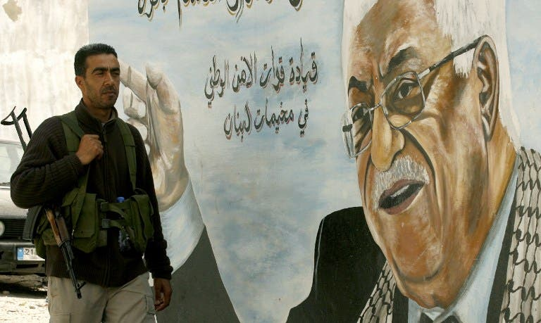 A Fatah movement member stands next to a mural of the Palestinian leader Mahmoud Abbas in the Ain al-Helweh Palestinian refugee camp on the outskirts of the southern Lebanese city of Sidon. (AFP PHOTO/MAHMOUD ZAYYAT)