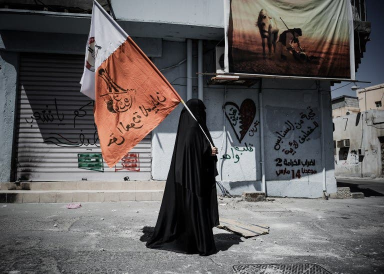 A Bahraini woman holds up her national flag decorated with anti-government slogans in the village of Jidhafs, west of Manama. (AFP PHOTO/MOHAMMED AL-SHAIKH)