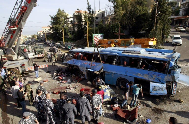 Lebanese security forces and civilians inspect the scene of a bus crash, killing and wounding several people, in the town of Kahaleh, ten kilometres east of Beirut on March 15, 2013, that was carrying Syrian refugees upon their arrival from Syria to Lebanon. (AFP PHOTO/ ANWAR AMRO)