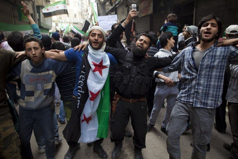 Syrian men dance and chant revolutionary slogans during the commemoration of the second anniversary of the Syrian conflict, in Bustan al-Qasr district of Aleppo. (AFP PHOTO/JM LOPEZ)