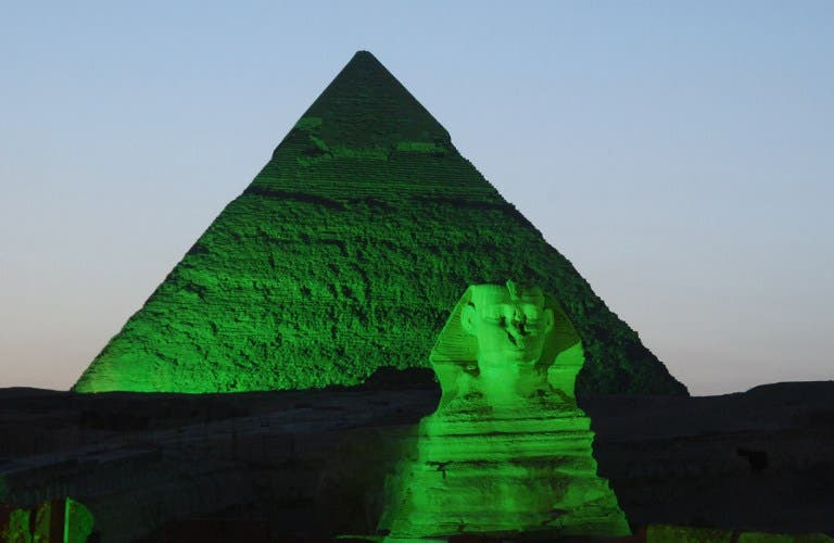 A picture shows one of the three Giza Pyramids and the Sphinx (foreground) lit in green on the occasion of St. Patrick's Day. (AFP PHOTO/IRISH EMBASSY/HO)