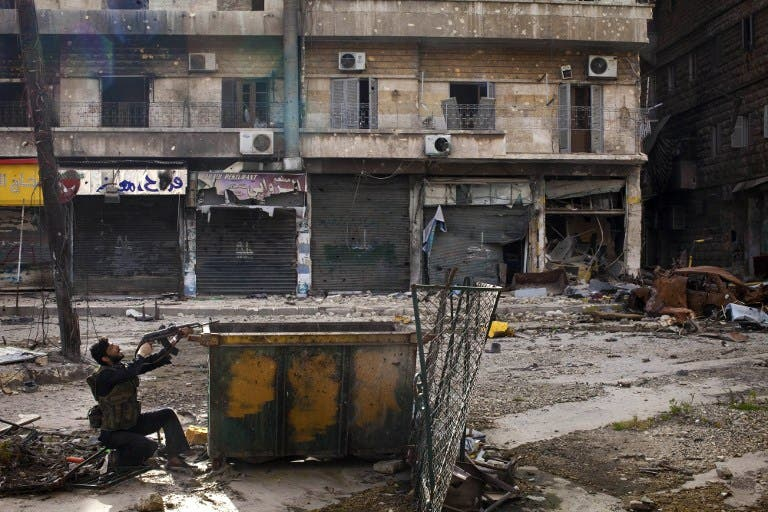 A Syrian rebel aims his weapon as he takes position behind a makeshift barricade during clashes with regime forces in the Salaheddine district of Aleppo. (AFP PHOTO/JM LOPEZ)