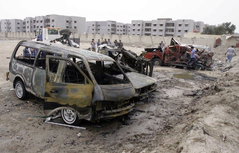 Iraqi emergency personnel and civilians gather around the site of a car bomb explosion near the outskirts of the south Iraq city of Basra, on March 17, 2013, killing 10 people and wounding 16, the head of the Basra provincial council security committee said. (AFP PHOTO/STR)
