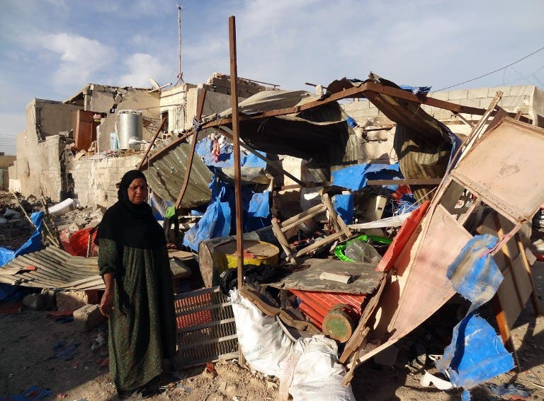An Iraqi woman inspects the damage following a car bomb attack that happened late at night in Kirkuk, 240 kilometers north of Baghdad, on March 20, 2013, that killed one and wounded several. (AFP PHOTO / MARWAN IBRAHIM)