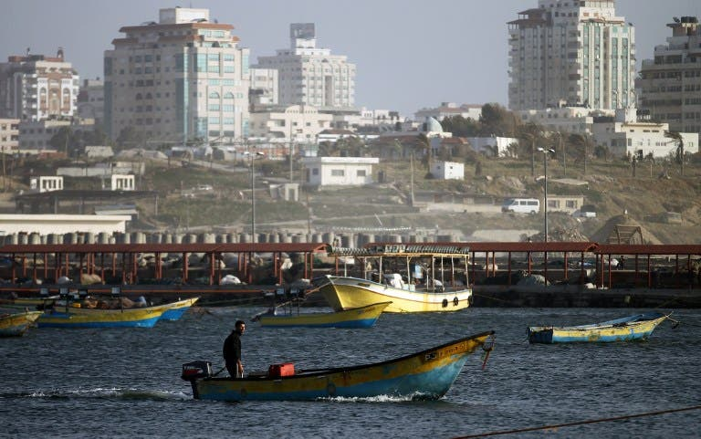 A Palestinian fisherman rides a boat near the port of Gaza City on March 22, 2013. Israel cut the distance from the shore that Gaza fishermen are allowed to sail from six to three miles and shut the Kerem Shalom goods crossing from Israel into the Gaza Strip in response to a rocket attack against southern Israel. (AFP PHOTO/MOHAMMED ABED)
