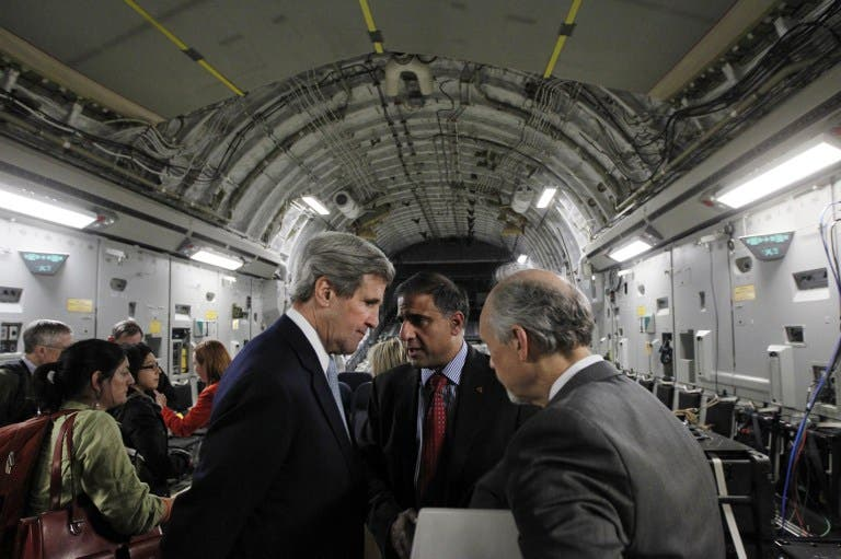 U.S. Secretary of State John Kerry speaks with Puneet Talwar (C), the National Security Council's Senior Director with responsibilities for Iran, Iraq, and the Gulf countries, and another advisor aboard an Air Force C-17 aircraft during their return to Amman from a trip to Baghdad. (AFP PHOTO/JASON REED/POOL)
