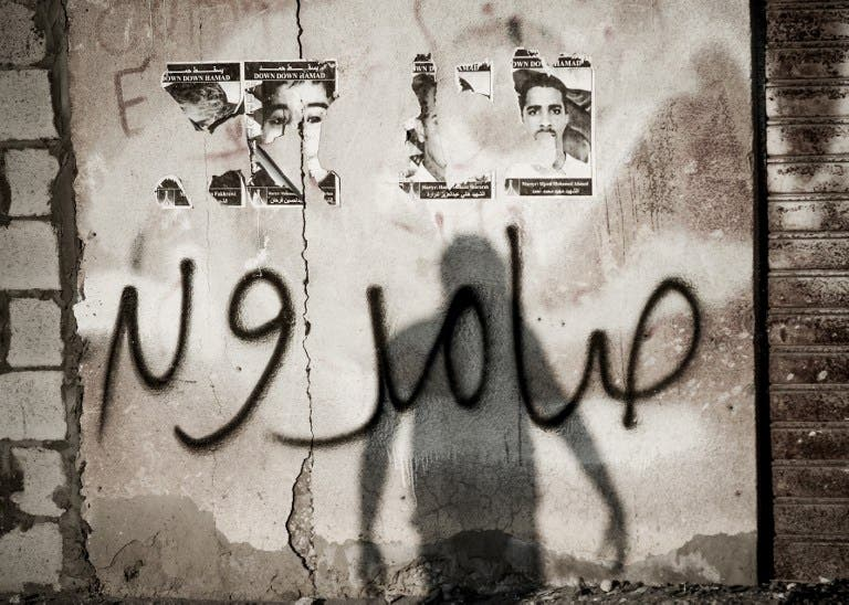 The shadow of a Bahraini protestor is seen over a graffiti which reads in Arabic