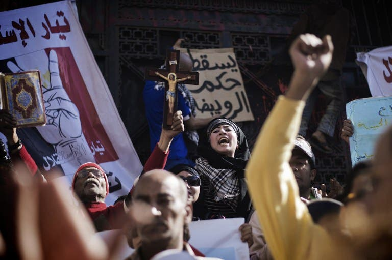 Egyptian political activists, victims and prisoners' relatives shout slogans during a protest against current prosecutor general Talaat Abdallah outside Cairo High Court on March 29, 2013 in Egypt. An Egyptian court on March 27 overturned a decision by President Mohamed Morsi to sack prosecutor general Abdel Meguid Mahmoud and ordered his reinstatement, state media reported. The ruling by the appeals court will once again put the presidency on a collision course with the judiciary, while any enforcement of its terms remains trapped in a legal labyrinth. (AFP PHOTO/GIANLUIGI GUERCIA)
