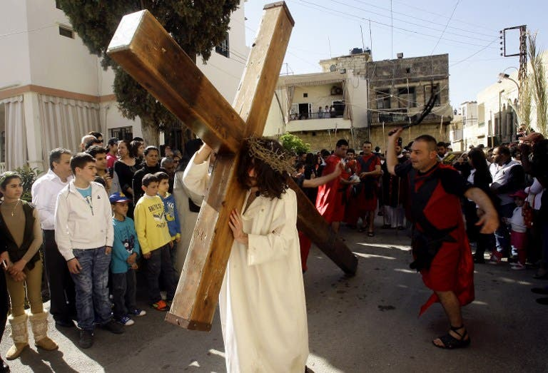A Christian man holds a large wooden cross as Lebanese Christians reenact the crucifixion of Jesus Christ during the Good Friday procession in the southern village of Qraiyeh. (AFP PHOTO/MAHMOUD ZAYAT)