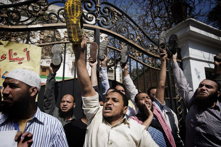 Egyptian protestors raise their shoes as they shout political and religious slogans outside the Iranian ambassador's residence in Cairo. (AFP PHOTO/GIANLUIGI GUERCIA)