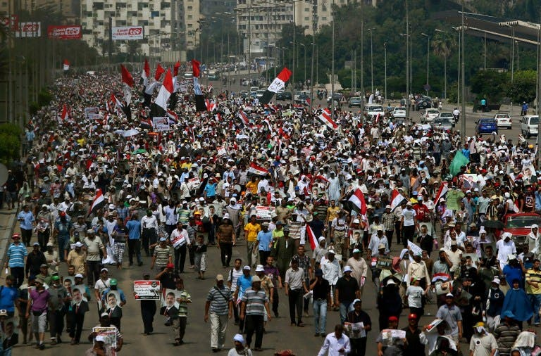 EGYPT, Cairo : Supporters of the Muslim Brotherhood and ousted Egyptian president Mohamed Morsi raise pictures of the toppled leader and wave the national flag during a demonstration in Cairo, on July 19, 2013. (AFP PHOTO /MARWAN NAAMANI)