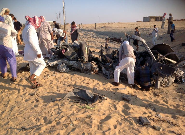 Egyptians gather near a damaged car bomb that exploded before reaching the intended target, killing three passengers on July 24, 2013 in El-Arish, in Egypt's Sinai peninsula. (AFP)