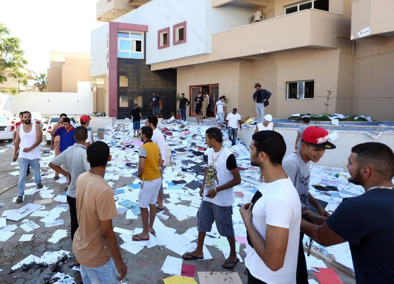 LIBYA, Tripoli : Libyan protesters stand amidst scattered documents after ransacking the offices of Muslim Brotherhood-backed Party of Justice and Construction, in the Libyan capital Tripoli on July 27, 2013. AFP PHOTO/MAHMUD TURKIA